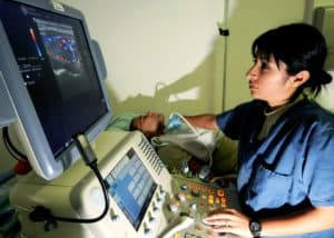 diagnostic medical sonographer salary:: A trained medical progessional earns her ultrasound tech salalry by performing an ultrasound on a patient.
